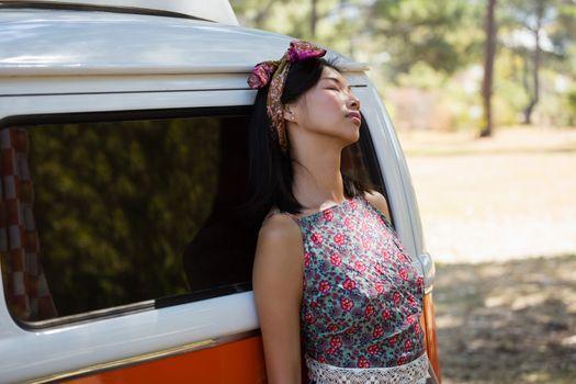 Woman relaxing on camper van in the park