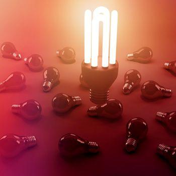 High angle view of lit energy efficient lightbulb over bulbs