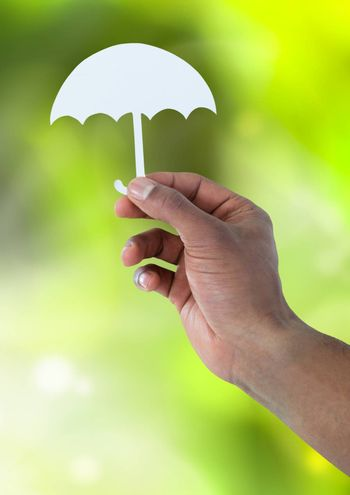 Digital composite of Cut out of umbrella in hand in nature