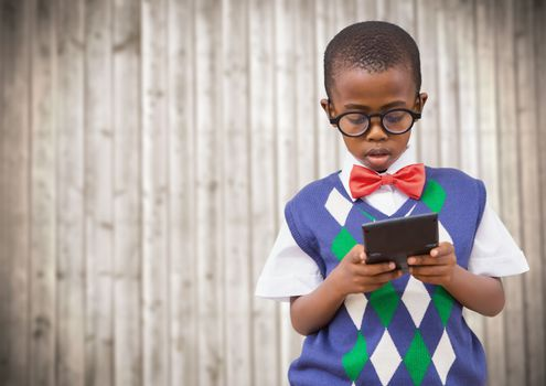 Boy in vest and bowtie with calculator against blurry wood panel