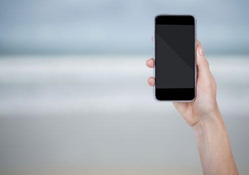 Hand with phone against blurry beach