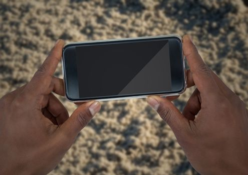 Hands with phone against blurry sand
