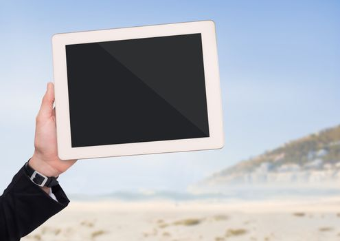 Hand with tablet against blurry beach