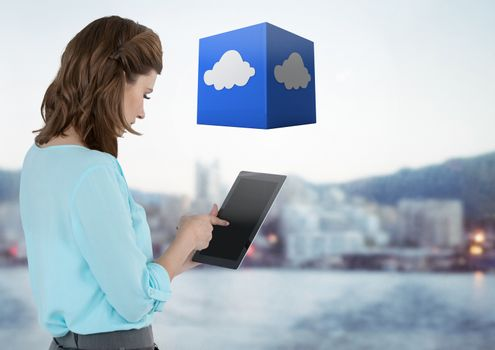 Businesswoman holding tablet with cloud cube with distant city background