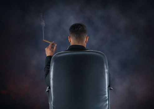 Businessman Back Sitting in Chair with cigar and dark smoky background
