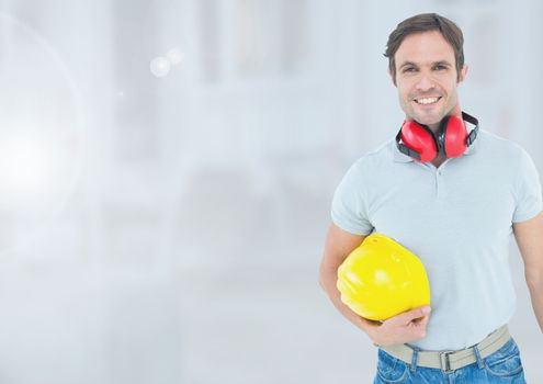 Construction Worker with ear protection in front of construction site