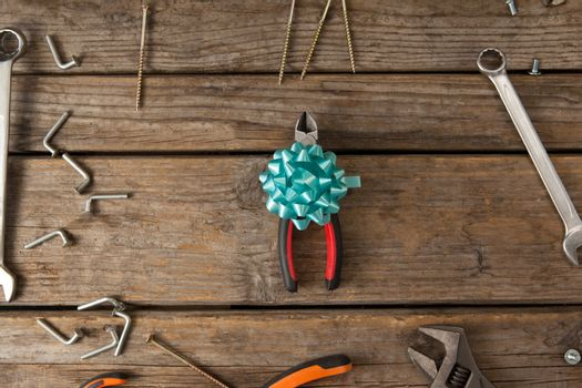 Pliers with ribbon amidst hand tools on table