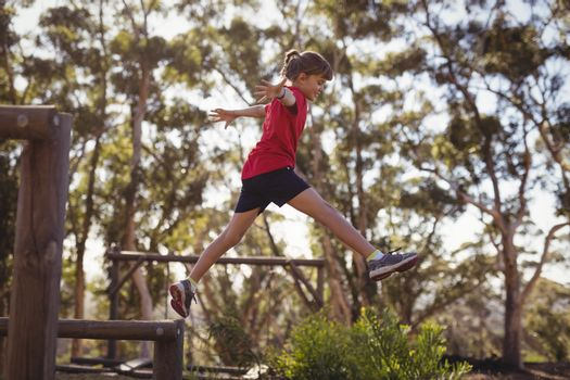 Determined girl jumping over obstacle