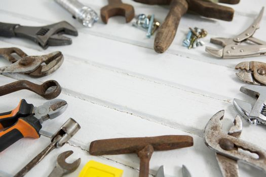 Various hand tools arranged on white table