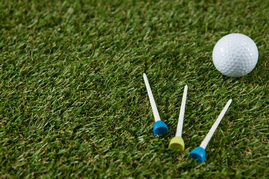 Golf ball with tee on grassy field
