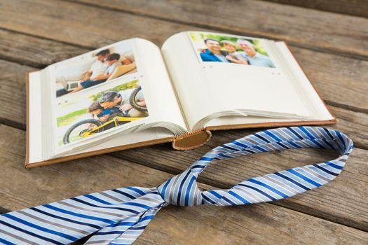Photo album with necktie on wooden table