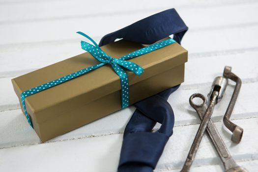 Close up of necktie and gift box by work tools