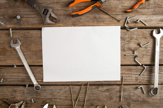 Blank paper amidst hand tools on table