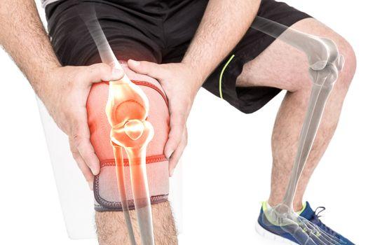 Man holding sore knee against white background