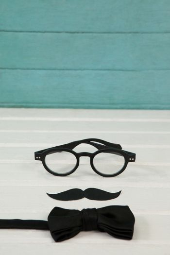 Eyeglasses with mustache and bowtie on table