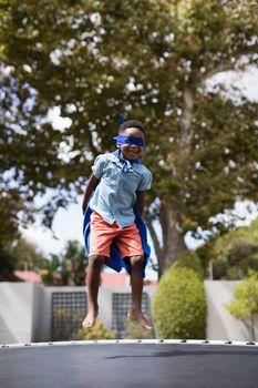 Boy in superhero costume jumping on trampoline