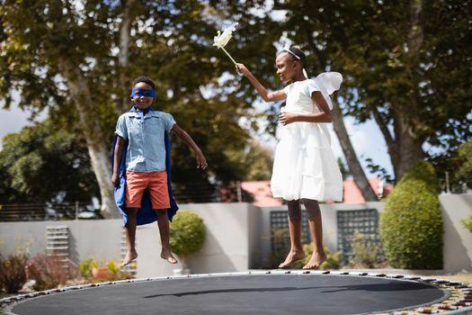 Siblings in costumes jumping on trampoline