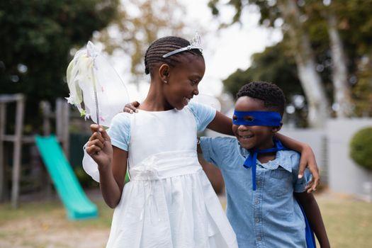 Siblings in costumes standing at park