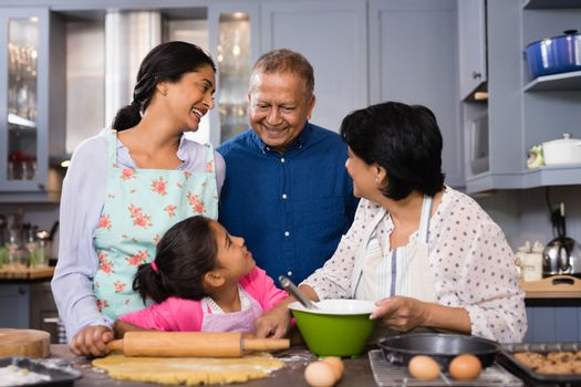 Portrait of multi-generation family standing together in domestic kitchen