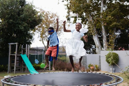 Playful siblings in costumes enjoying on trampoline
