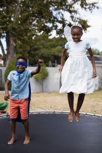 Siblings in costumes jumping on trampoline at lawn