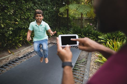 Father photographing son while jumping on trampoline at park