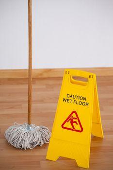 Mop with wet floor caution sign