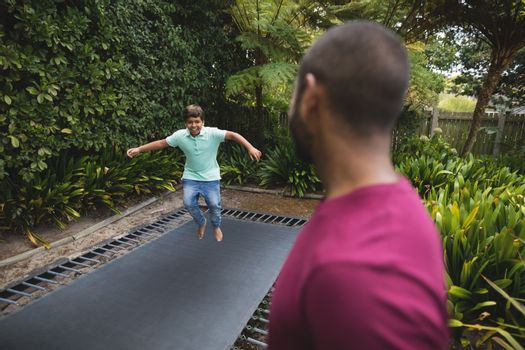 Father looking at son jumping on trampoline