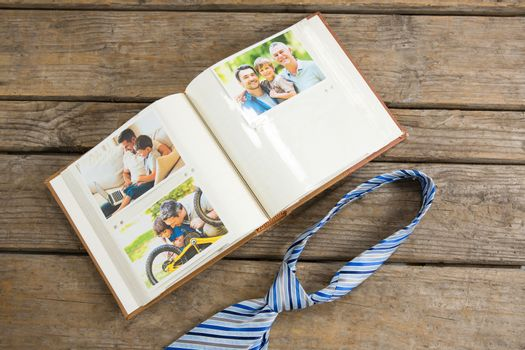 Overhead view of photo album by necktie on table