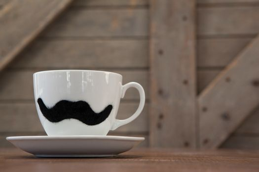 Cup and saucer with fake moustache