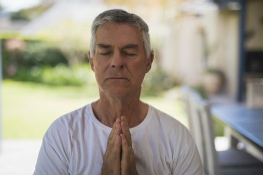 Senior man meditating at porch