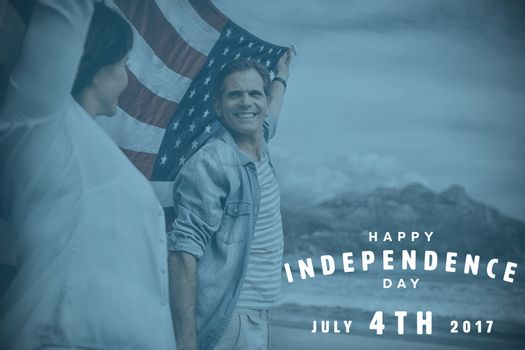 Happy 4th of july text on white background against mature couple holding american flag on beach