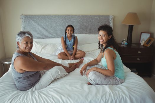 Happy family sitting on bed in bed room