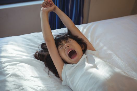 Girl yawning on bed in the bed room