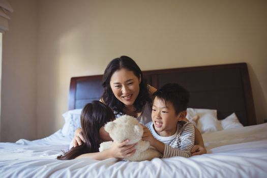 Happy family having fun on bed in bed room