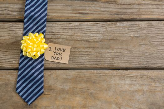 Overhead view of necktie with greetings on table