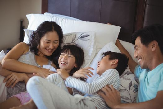 Happy family having fun on bed in the bed room