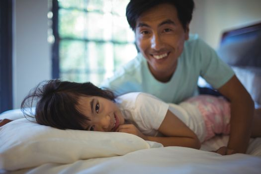Father and daughter having fun on bed in bed room