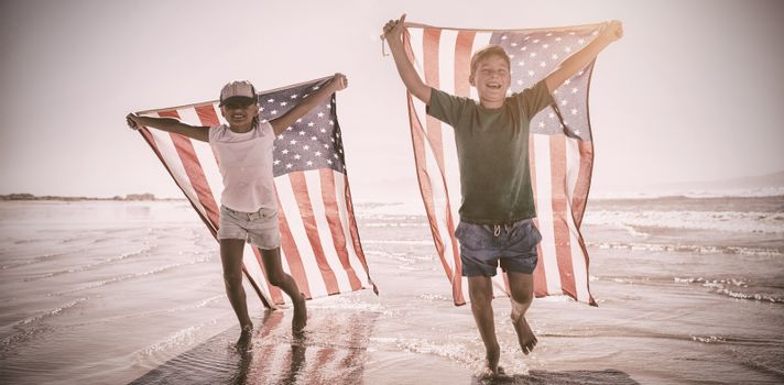 Happy children taking an american flag on the beach