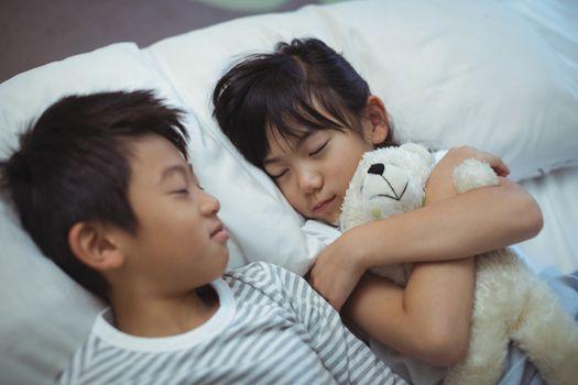 Siblings sleeping on bed in the bed room