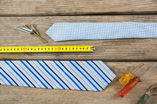 Overhead view of hand tools and neckties on table
