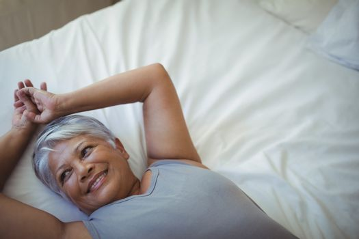 Senior woman relaxing on bed in bed room