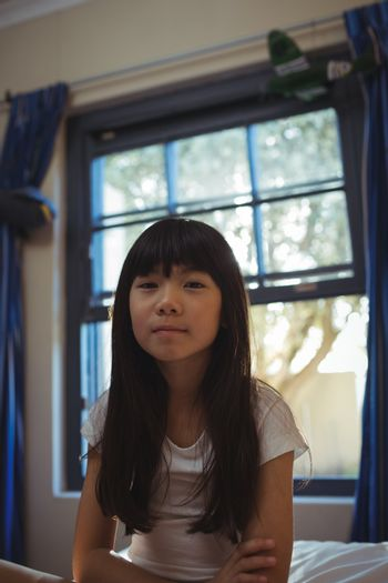 Smiling girl sitting on bed in the bed room