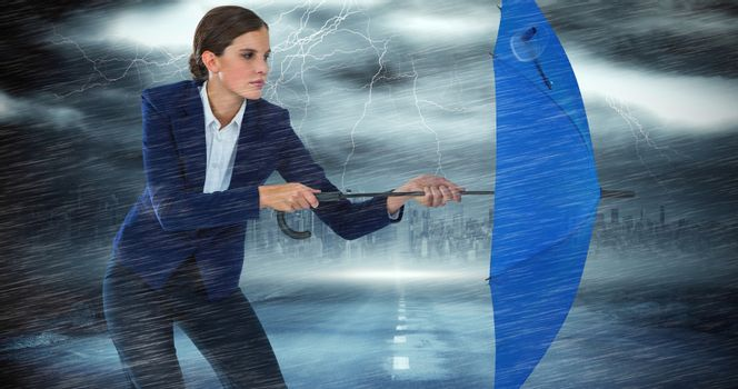 Composite image of confident businesswoman defending with blue umbrella