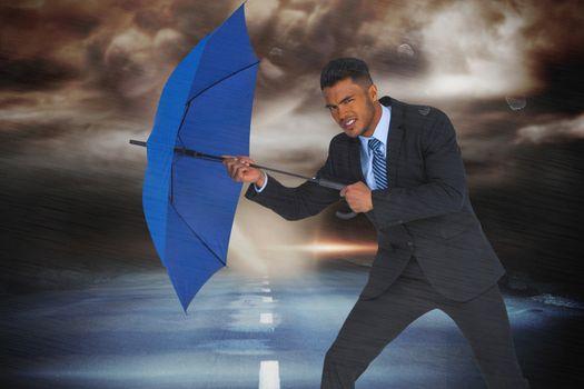 Composite image of portrait of businessman defending with blue umbrella