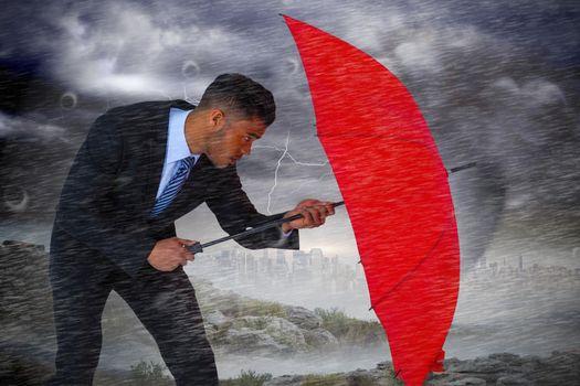 Composite image of businessman defending with red umbrella