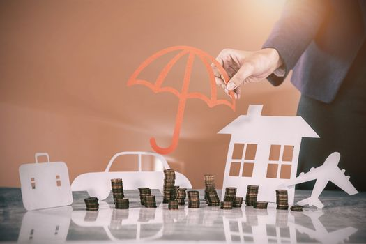 Composite image of businesswoman protecting her wealth with umbrella