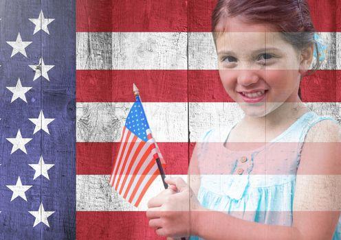 Little girl holding american flag against american flag