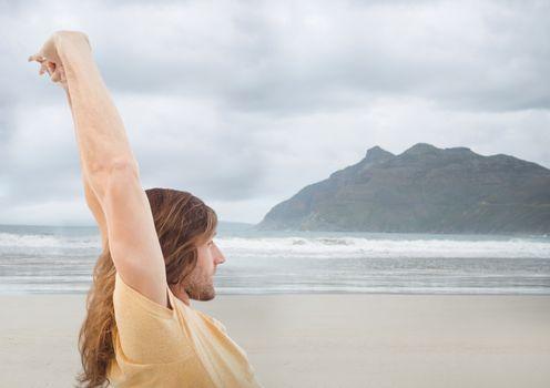 Man stretching against blurry beach