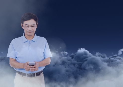 Man texting in darkness with clouds in background